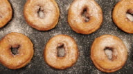 TOP VIEW: Dolly shot of a rows of doughnuts with sugar powder on the black desk video