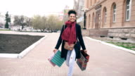 Dolly shot of Attractive mixed race girl dancing and have fun while walking down the street with bags. Happy young woman walking after shopping on mall sale video