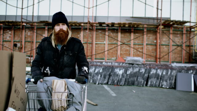 Dolly shot of bearded homeless man walking down the street with shooping card at cold autumn day video