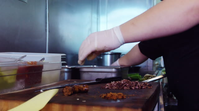 Dolly Shot of Chef Slicing Chorizo in Restaurant Kitchen video
