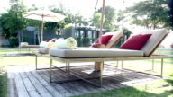 Dolly shot of modern sunbeds beside swimming pool video