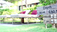 Dolly shot Of modern sunbeds beside the sign of swimming pool sign video