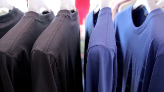 Dolly Shot of T-shirts on a coat rack video