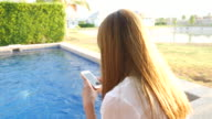 Dolly Shot:Youngwoman using smartphone by the swimming pool video