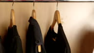 Dolly: Some black and one white t-shirt on a hangers in wardrobe video