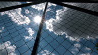 Dolly: Sun shining through the chain link iron wire fencing video