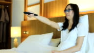 HD Dolly: Woman lying on the bed And use the TV remote video