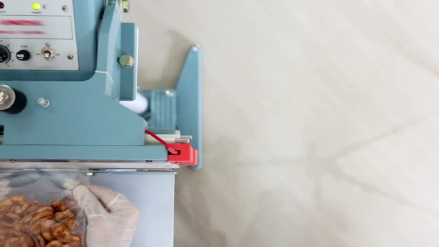 Dolly: Worker using Thermal Sealer to seal Food Package video