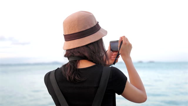 HD Dolly:Woman using a digital camera taking pictures of the sea. video