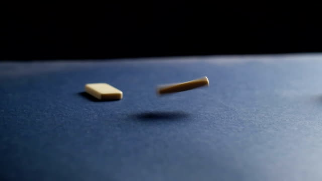 Dominoes falling on the table. Slow motion video