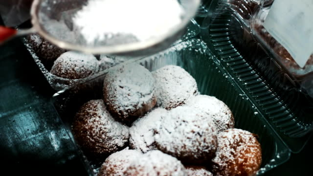 Donuts are sprinkled with snow-white sugar powder and packed. Fatty delicious pastries, food. sweetness video