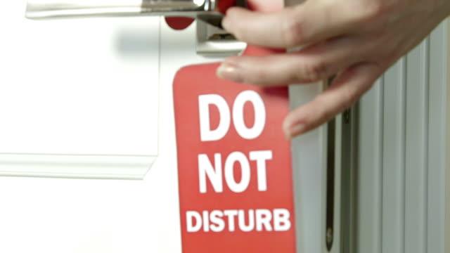 Door hanger do not disturb on handle of a hotel room video
