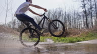 SLO MO Downhill biker performing wheelie through a puddle video