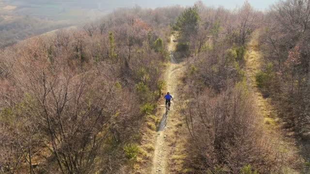 HD: Downhill Mountain Biker Speeding Along Trail video