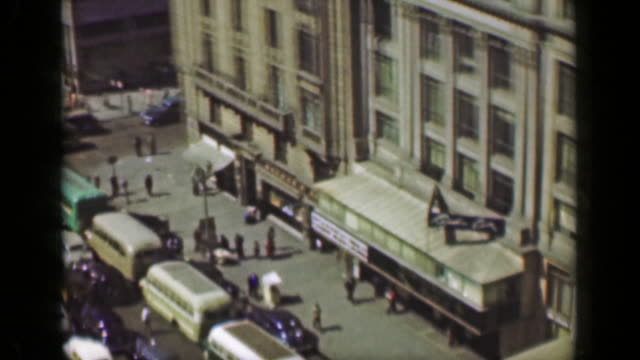 1952: Downtown building architecture busy car traffic municipal park square. video