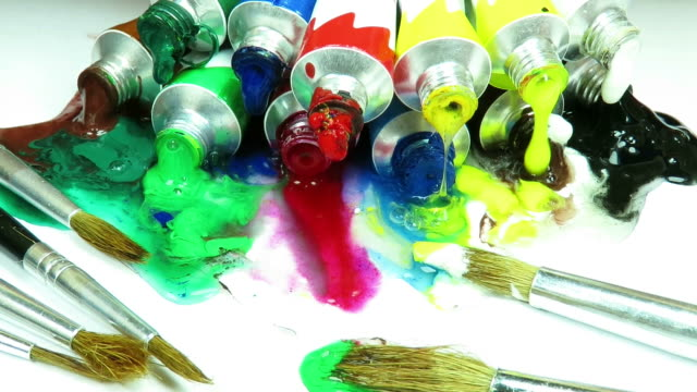 Dozen of acrylic paint tubes in different colors , being squeezed and the paint coming out of them and blending on a white surface, with several paint brushes aside video