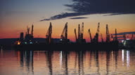 Dramatic sunset over the sea port and cranes video