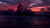 SLOW MOTION: Dramatic view of big wave crashing into coral reef under pink skies video