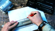 Drawing a pencil line on the ruler on the drawing sheet. video