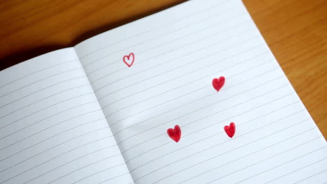 drawings of red hearts appear on a notepad video