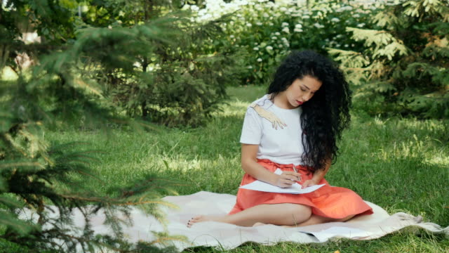 Dreamy curly girl writes poems in park on plaid video