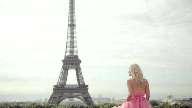 Dreamy girl in the lush pink long dress looking at the Eiffel Tower in Paris video