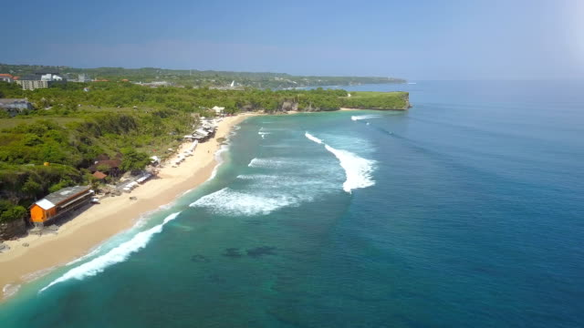 AERIAL: Dreamy sandy beach, surf cabins and crowded lineup in sunny Bali ocean video