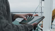 Dressed in Protective Coat Fisherman Using Tablet Computer with Navigation Maps while Traveling on Ship. video