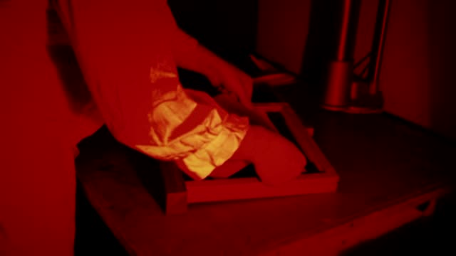 dressing sheet film for the camera in the darkroom video