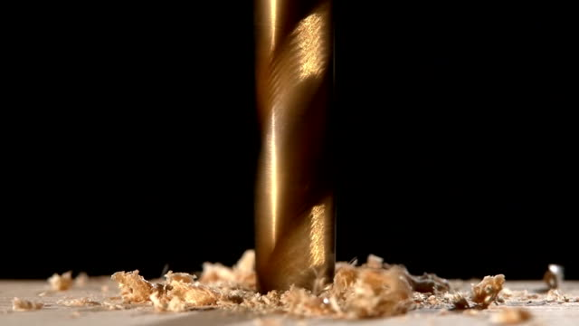 Drill with sawdust on wooden plate black, close up video
