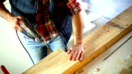 Drilling holes in a wood plank. video