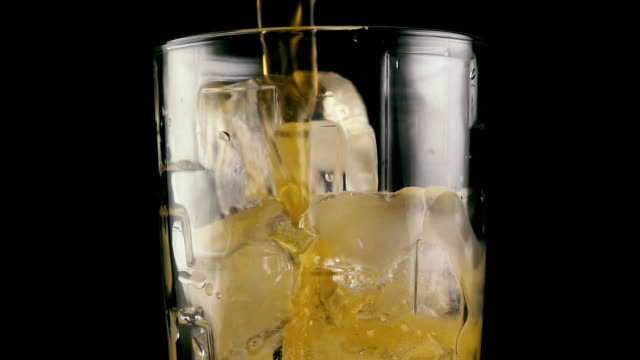 A drink flows into the glass with ice. Slow mo video