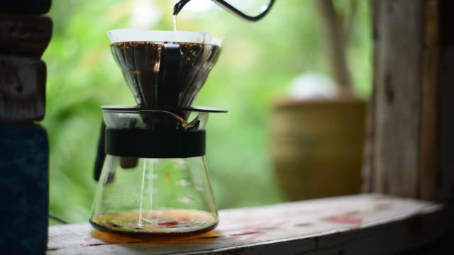 Drip coffee process, The man pouring hot water over the ground on the vintage window. video