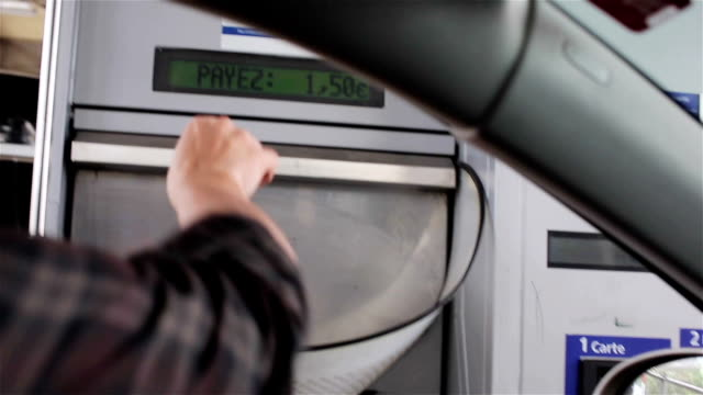 Driver hand toss coins in toll road booth basket in France Europe. Stop to pay toll fee throwing cash to collector target bin moving to gate. Unmanned automatic payment machine at toll plaza turnpike video
