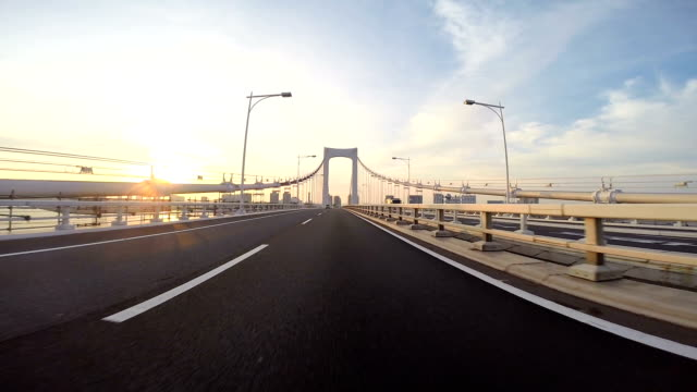 Driver's POV heading towards the sunrise over the Rainbow Bridge. video