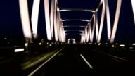 Driver's POV through the bridge above water at twilight. video