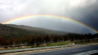 POV driving along highway as rainbow forms overhead video