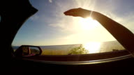 SLOW MOTION: Driving along the beach at sunrise hand waving in the summer wind video