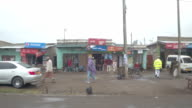 CLOSE UP: Driving on muddy road past colorful street stores in poor African town video