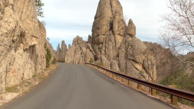 POV: Driving on Needles Highway past majestic rocky spires above the steep abyss video