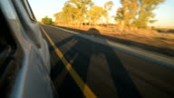 Driving through beautiful and sparse South African landscape at sunset on a highway next to countryside video