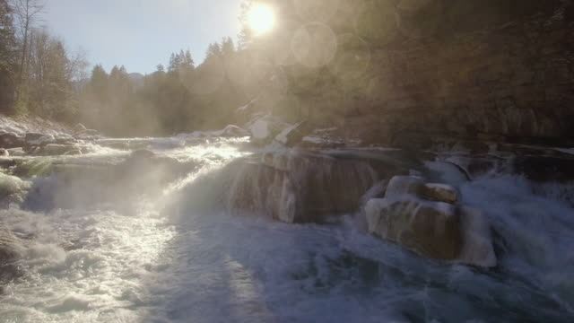 Drone Floating Low Getting Wet Over Raging River Rapids with Ice and Snow video