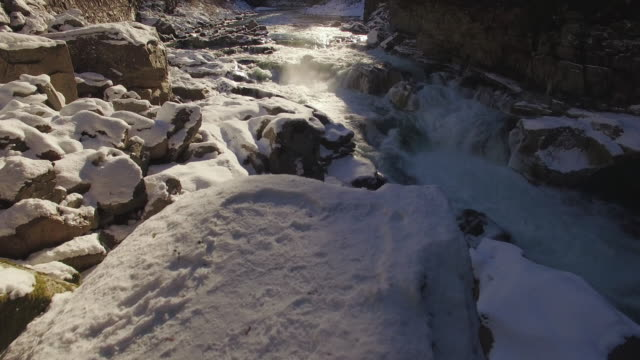 Drone Floating Over Snowy Rocks to Reveal Raging River in Winter Season video