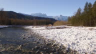 Drone Flying from River Up to Mountains with Winter Snow and Blue Sky video