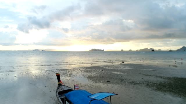 Drone flying over long tail boat in Thailand at sunrise video