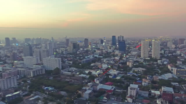 WS Drone flying, Top view of skyscraper which sunset Golden light though clouds over cityscape. video