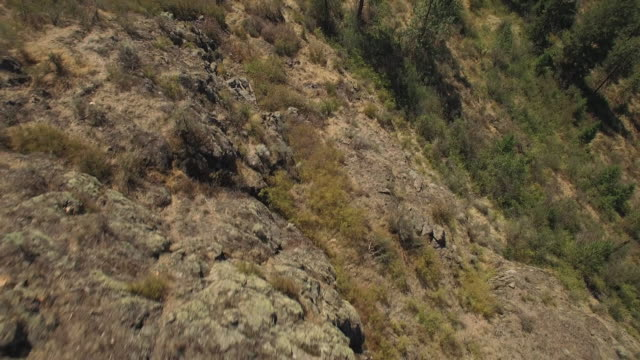 Drone Pilot Flying with Remote on Top of Rocky Mountain Cliff video