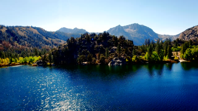 Drone risings over lake in the wilderness with fishermen fishing in the morning sun. video