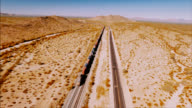 Drone shot following a large container locomotive in the barren American desert. video