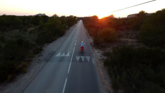 Drone shot following a scooter on a road through trees video